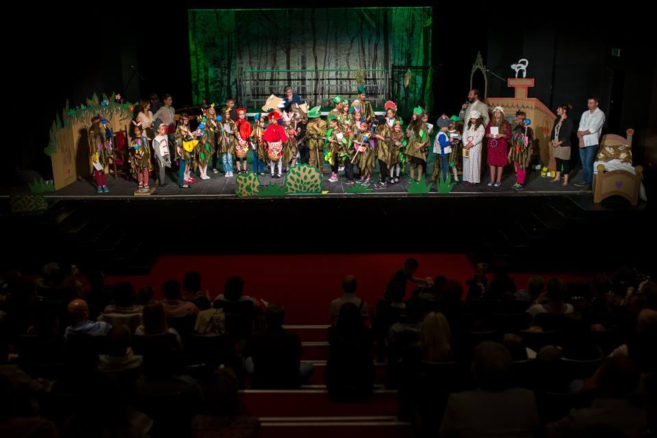 Obraz przedstawia salę teatralną z widownią, na scenie widnieją aktorzy jak i dzieci z placówki, które brały w tym dniu udział w przedstawieniu.