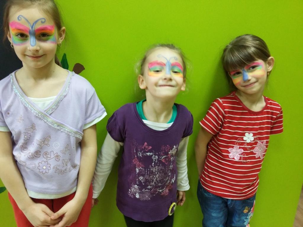 Zdjęcie przedstawia dzieci z pomalowanymi twarzami cieszące się wiosną.