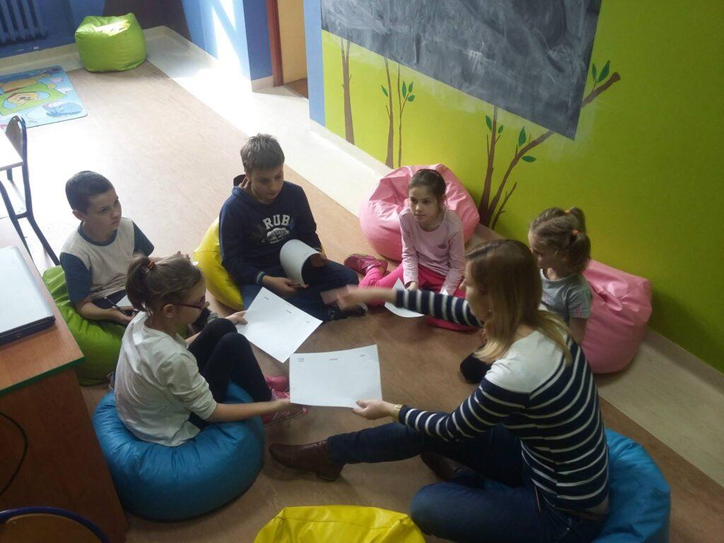 Zdjęcie przedstawia dzieci siedzące w kółku z osobą prowadzącą zajęcia. Zajęcia były o tematyce poczucia własnej wartości.
