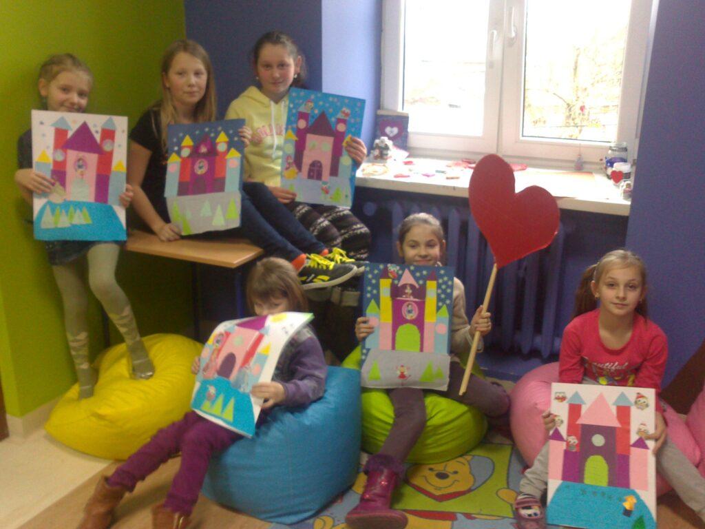 """Zdjęcie przedstawia dzieci z placówki trzymające ich dzieła powstałe w ramach akcji """"Radłów dzieli się miłością!"""""""