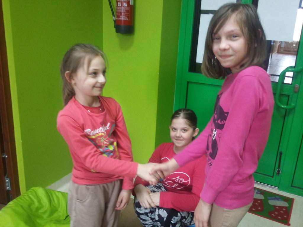 Zdjęcie przedstawia trzy dziewczynki przy wejściu, dwie z nich podają sobie ręce, natomiast trzecie siedzi w oddali.