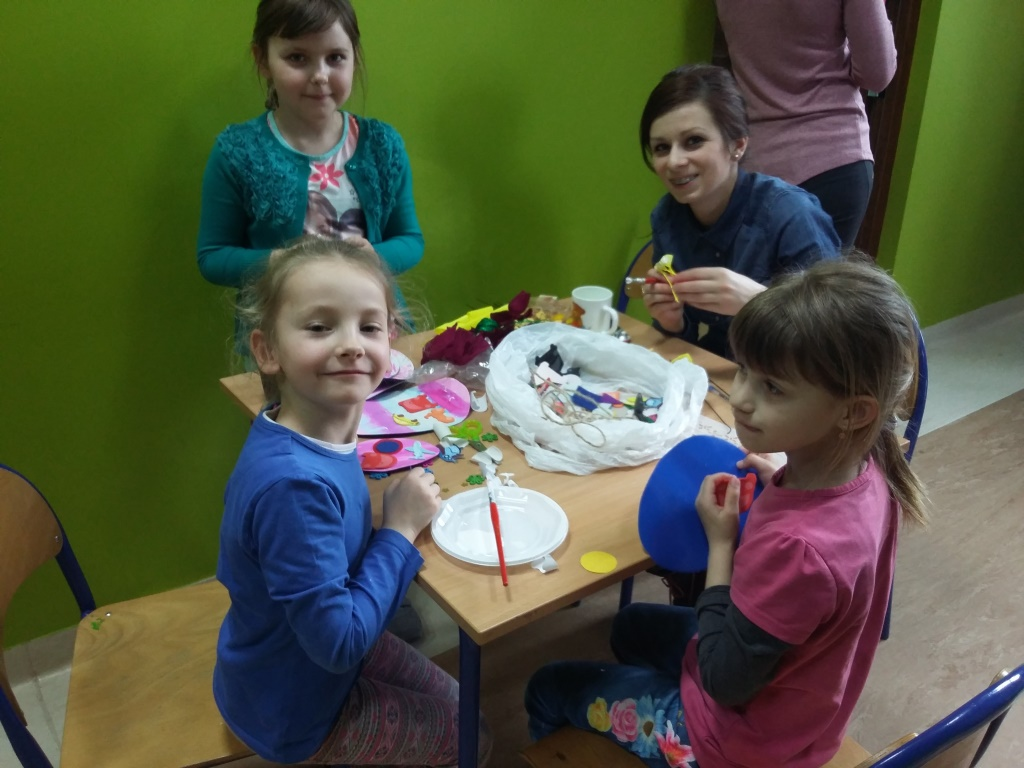 Zdjęcie przedstawia dzieci z placówki tworzące dekoracje świąteczne.