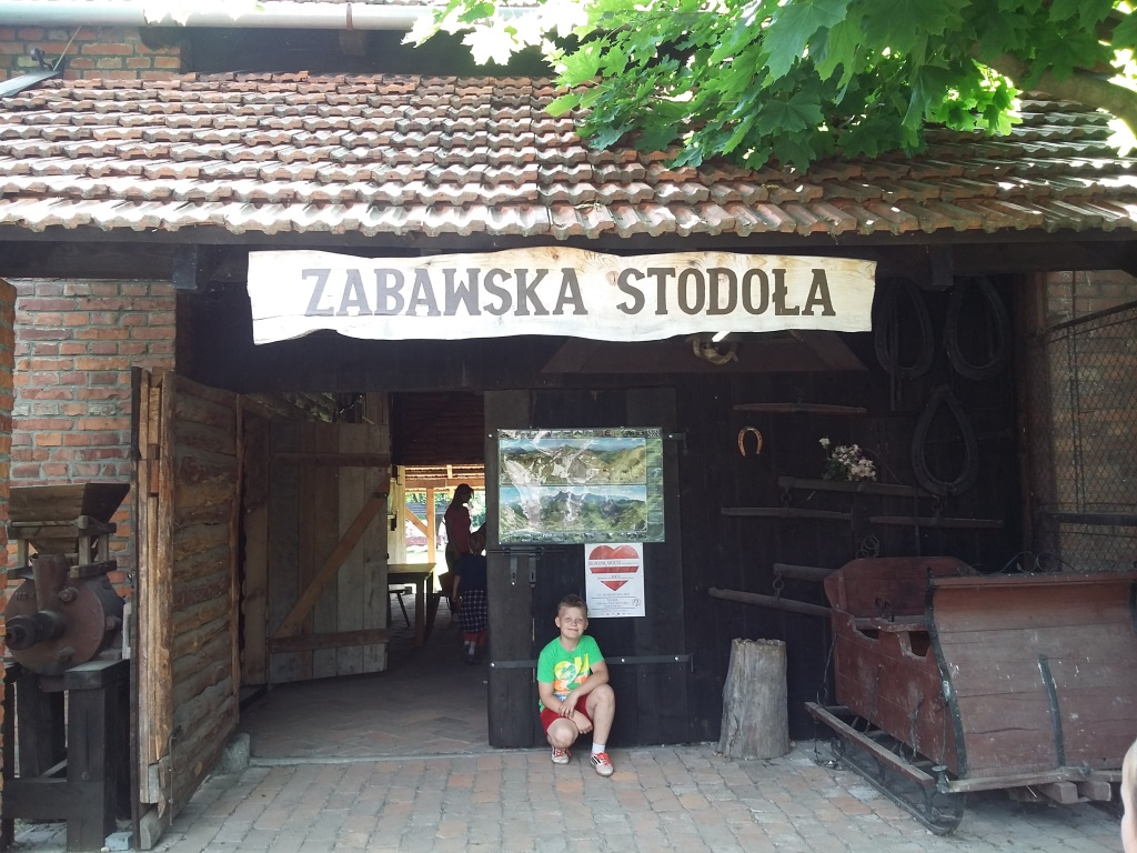 Zdjęcie przedstawia chłopca pozującego do zdjęcia w miejscowości Zabawa przy obiekcie Zabawska Stodoła
