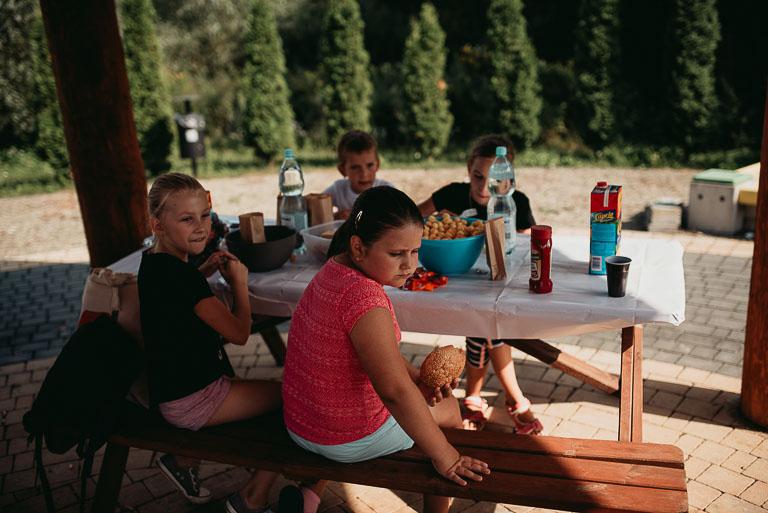 Obraz przedstawia poczęstunek zorganizowany na pikniku.