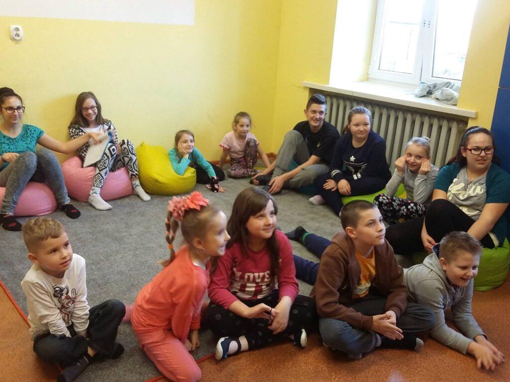 Zdjęcie przedstawia dzieci z placówki siedzące na dywanie w pomieszczeniu z żółtymi ścianami podczas zajęć.
