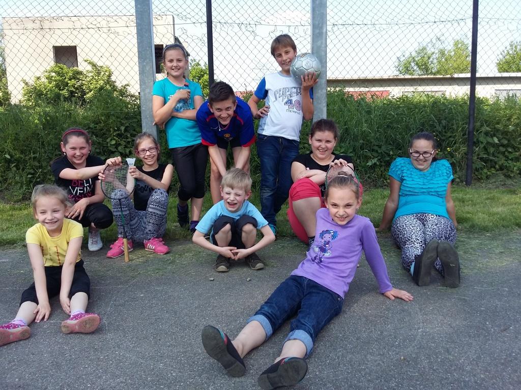 Zdjęcie przedstawia dzieci pozujące do zdjęcia w plenerze ze sprzętami sportowymi.