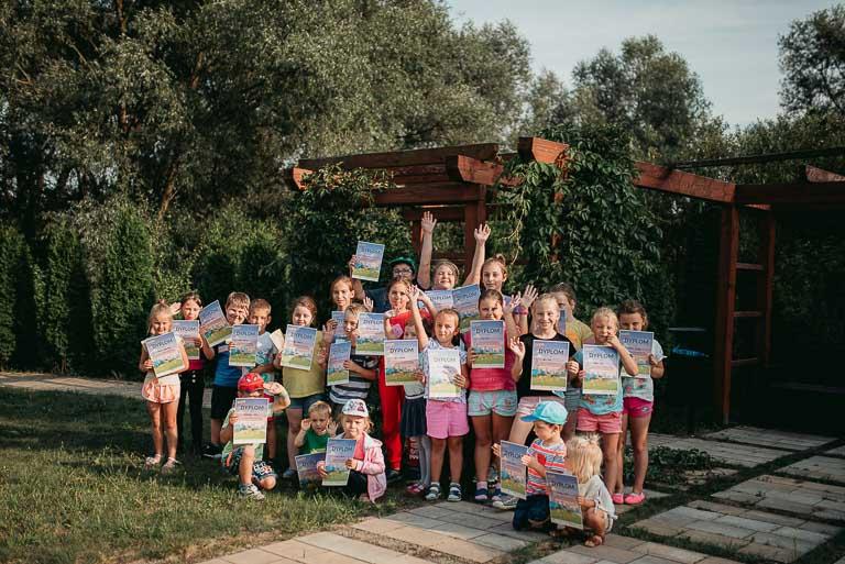 Obraz przedstawia wychowanków z dyplomami za uczestnictwo w pikniku.