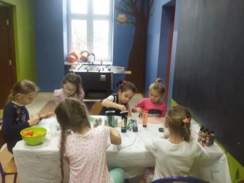 Zdjęcie przedstawia dzieci przy stole w niewielkim kolorowym pokoju, które tworzą prace plastyczne.