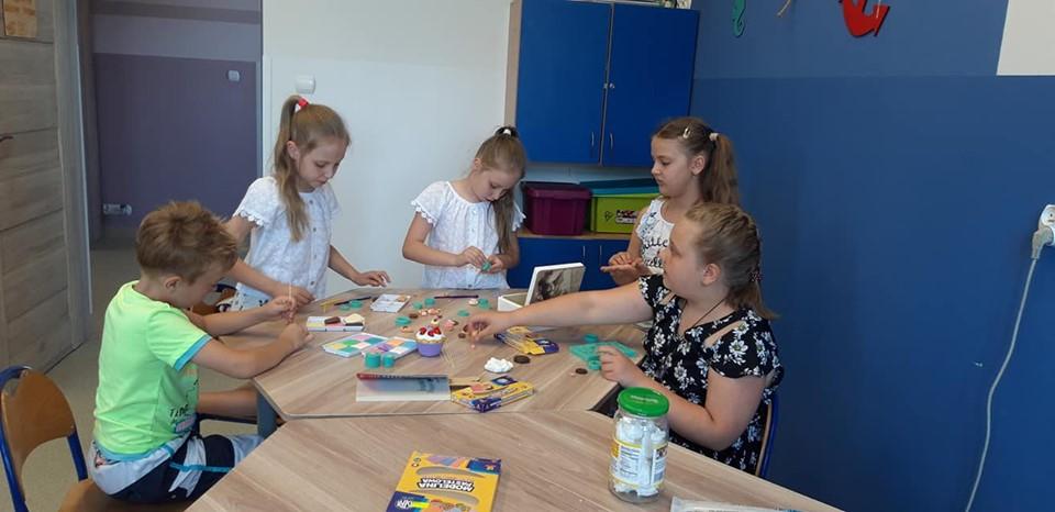 Obraz przedstawia wychowanków SPWD podczas zajęć artystycznych, na których tworzą one różnego rodzaju rękodzieła przy użyciu modeliny czy masy modelarskiej.