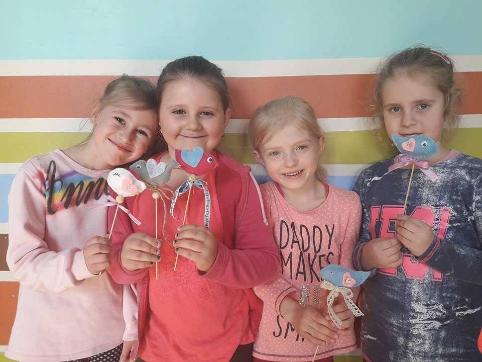 Zdjęcie przedstawia dzieci z placówki na tle ściany z kolorowymi paskami, które trzymają ozdoby na cienkich patyczkach.