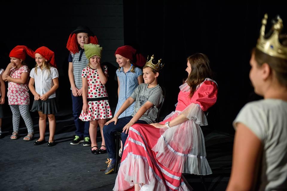 Zdjęcie przedstawia dzieci w przebraniach na scenie teatru.