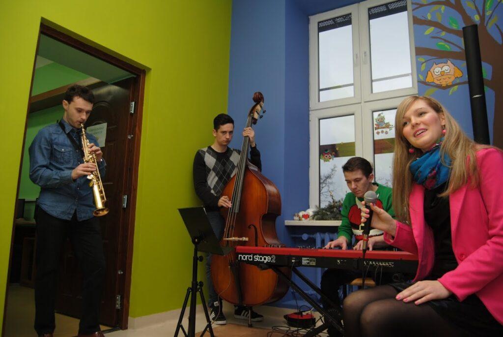 Obraz przedstawia osoby grające na instrumentach oraz śpiewające.