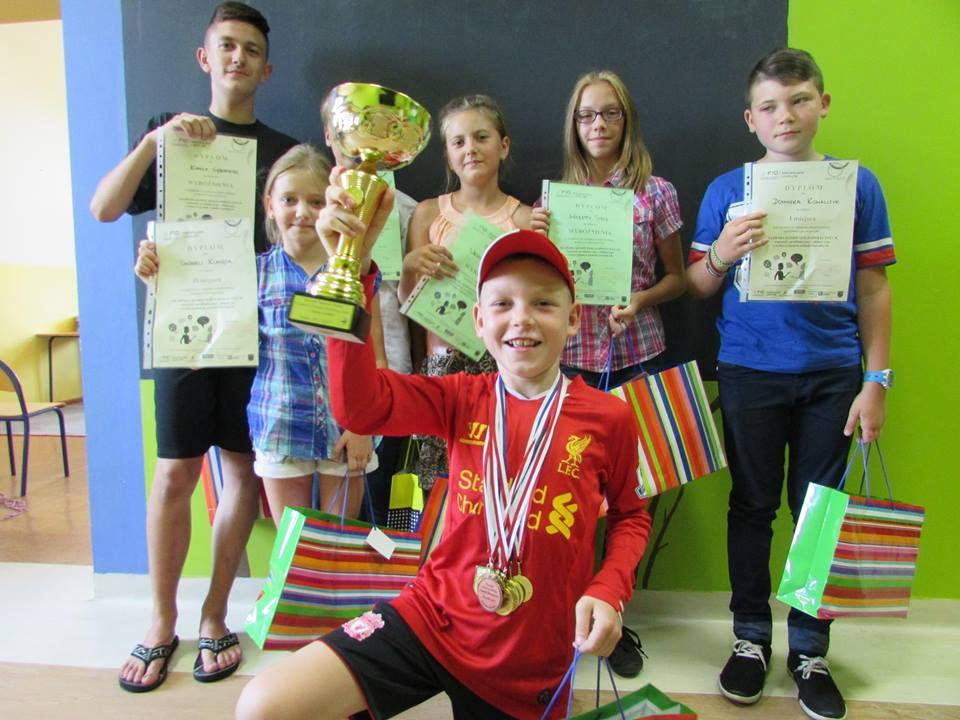 Zdjęcie przedstawia dzieci z placówki z dyplomami oraz nagrodami.