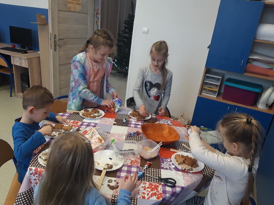 Na zdjęciu widać piątkę dzieci przy stole przygotowujące pierniki.