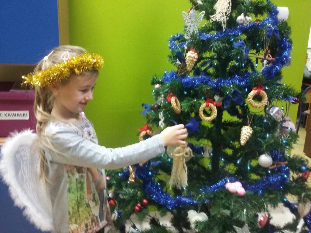 Zdjęcie przedstawia dziewczynkę w skrzydłach anioła ubierającą choinkę na tle zielonej ściany.