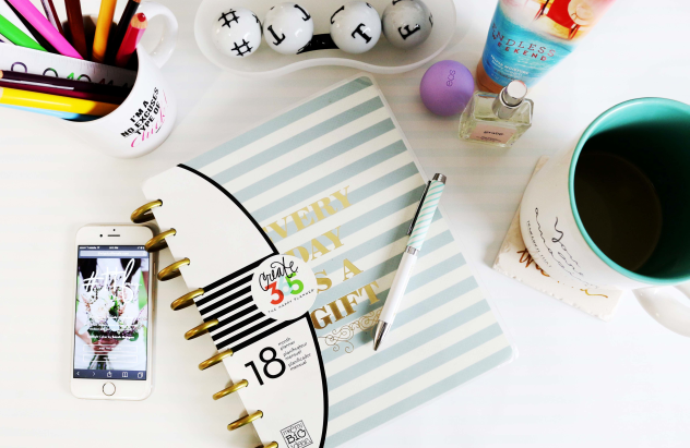 Grafika dekoracyjna z kubkiem, pisakami, telefonem, długopisem oraz zeszytem.