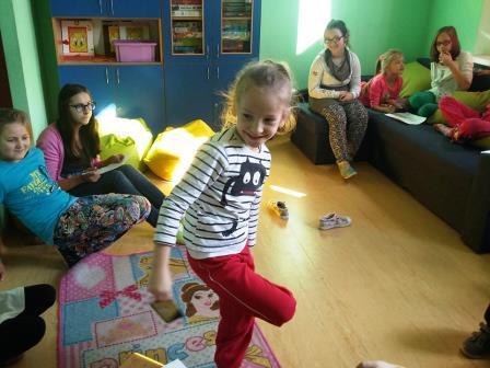 Zdjęcie przedstawia wnętrze jednego z pokoi w którym dzieci spędzają czas, również one są tam obecne wraz z opiekującymi się nimi osobami.