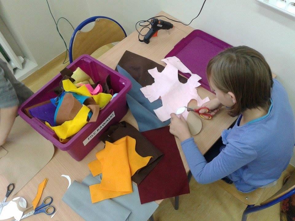 Zdjęcie przedstawia osobę wycinającą kawałek z większego materiału w kolorze białym. Obok w pudełku więcej kolorowych kawałków materiału.