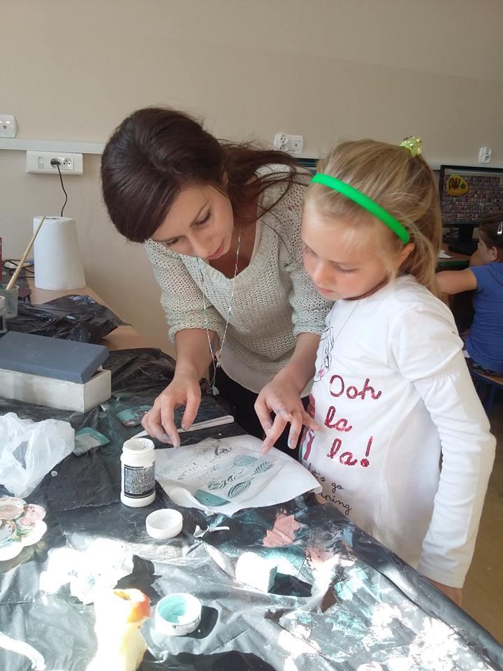 Zdjęcie przedstawia dziewczynkę oraz opiekunkę podczas warsztatów Kraina Rozmaitości razem tworzących rękodzieła przy stole z czarnym nakryciem.