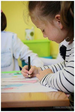 Zdjęcie przedstawia dziewczynkę malującą obrazek czarną kredką.
