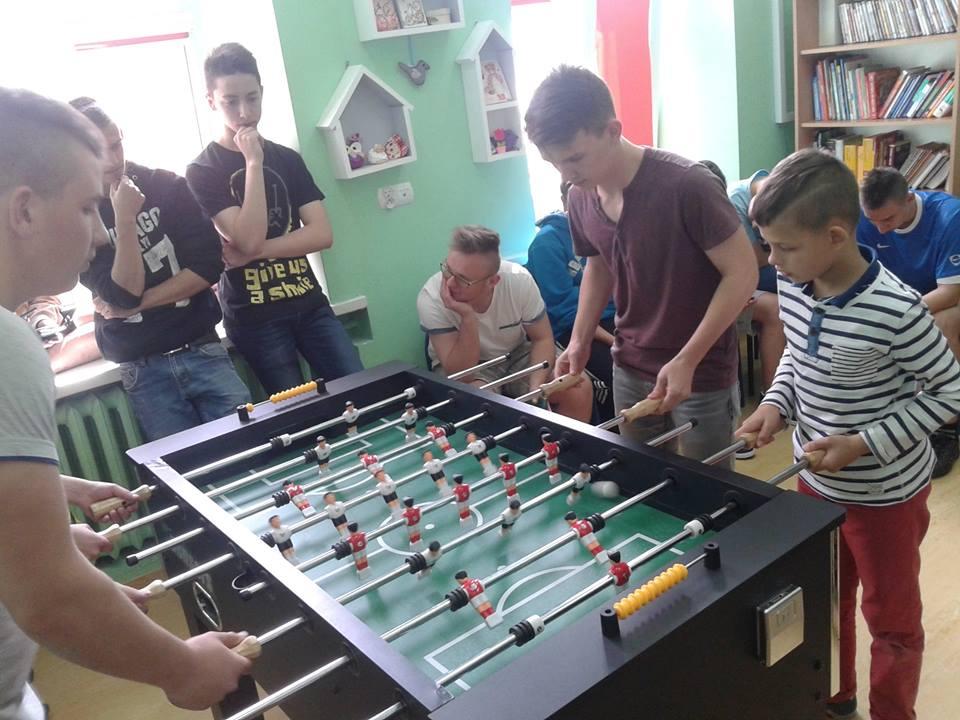 Na zdjęciu widnieje kilku chłopców z placówki grających w piłkarzyki na specjalnym do tego stole.