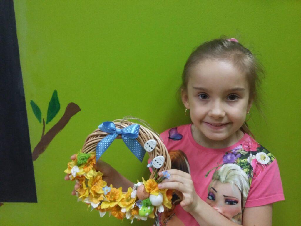 Zdjęcie przedstawia dziewczynkę trzymającą dekorację Wielkanocną na tle zielonej ściany.