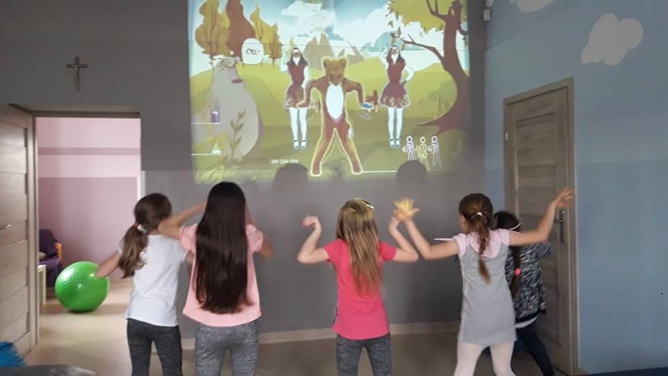 Obraz przedstawia wychowanków podczas zabaw z wykorzystaniem projektora. Na zdjęciu dzieci tańczą do filmiku wyświetlonego na ścianie przy użyciu projektora.