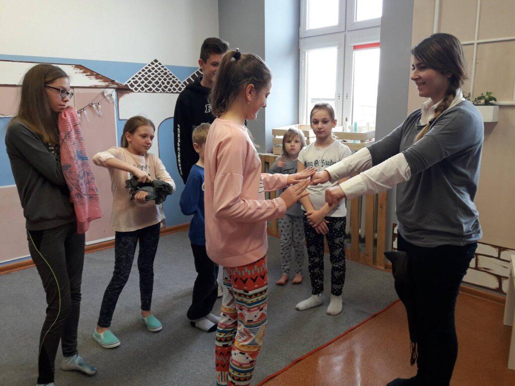 Zdjęcie przedstawia dzieci z placówki wraz z osobą prowadzącą zajęcia. Wszyscy stoją w pokoju z szarymi i białymi ścianami.