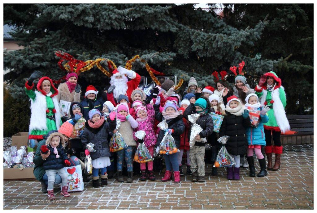 Zdjęcie przedstawia dzieci z placówki na zewnątrz przy dużym drzewie iglastym wraz z św. Mikołajem, który w tym dniu obdarował je prezentami.