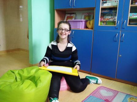 Zdjęcie przedstawia dziewczynkę siedzącą na tle niebieskich szafek, która trzyma w rękach podkładkę a na niej kartkę papieru.