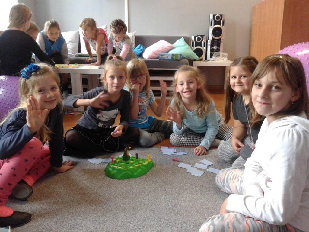 Na zdjęciu widnieje grupka dzieci siedzących na dywanie oraz grających w grę planszową. W oddali widać drugą grupkę dzieci, które również grają w inną grę.