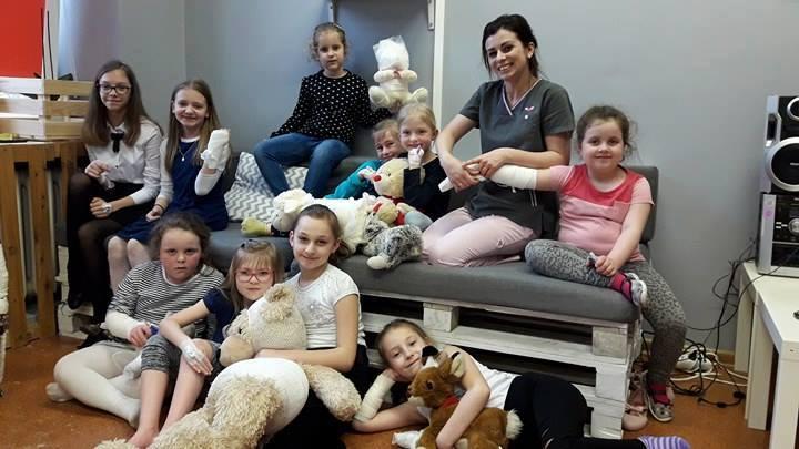 Zdjęcie przedstawia dzieci z placówki oraz osobę opiekującą się nimi siedzących na kanapie z palet oraz przed nią. Wszystko jest na tle szarej ściany.