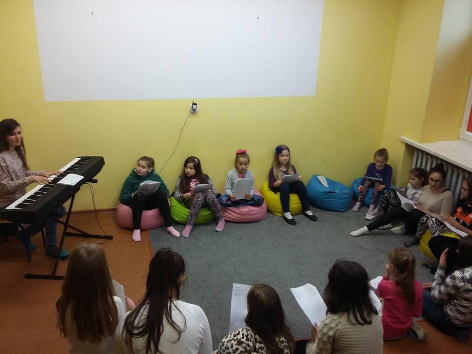 Zdjęcie przedstawia dzieci z placówki w pokoju z żółtymi ścianami podczas przygotowań do koncertu.