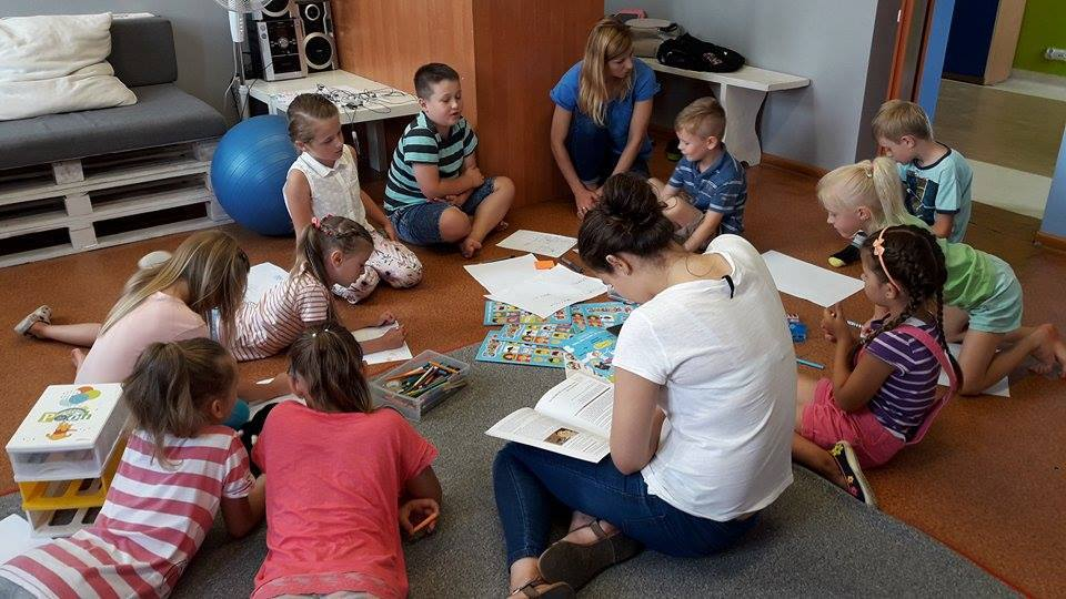Na zdjęciu widnieje grupka dzieci spędzających czas wraz z osobą opiekująca się nimi. Dzieci na siedzą na podłodze z kartkami oraz czymś do pisania oraz malowania.