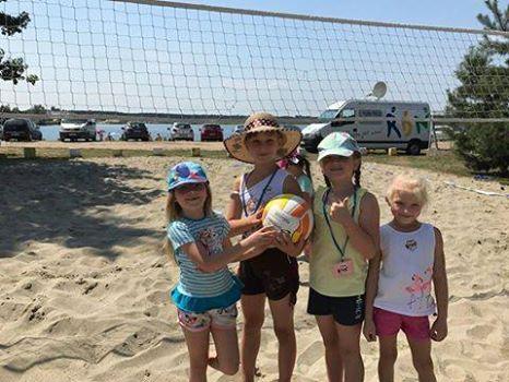 Na zdjęciu widnieją 4 dziewczynki trzymające piłkę do siatkówki na piaskowym boisku do siatkówki.