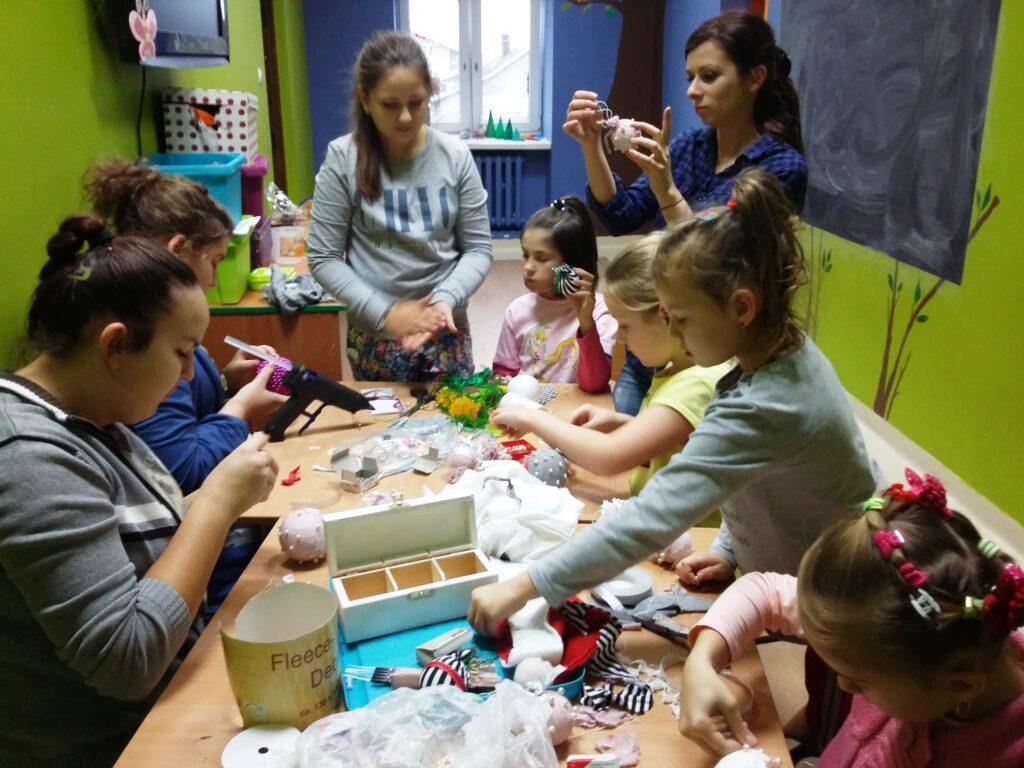 Zdjęcie przedstawia dzieci z placówki w sali zajęciowej z zielonymi ścianami, robiące dekoracje z okazji zbliżających się świąt.