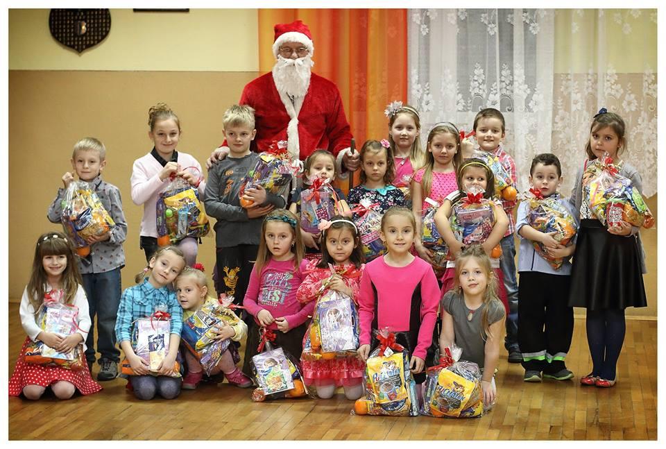 Zdjęcie przedstawia dzieci z placówki ustawione do zdjęcia z świętym Mikołajem oraz prezentami od Niego.