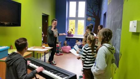 Zdjęcie przedstawia dzieci uczestniczące w warsztatach wokalnych w placówce wraz z instruktorem.