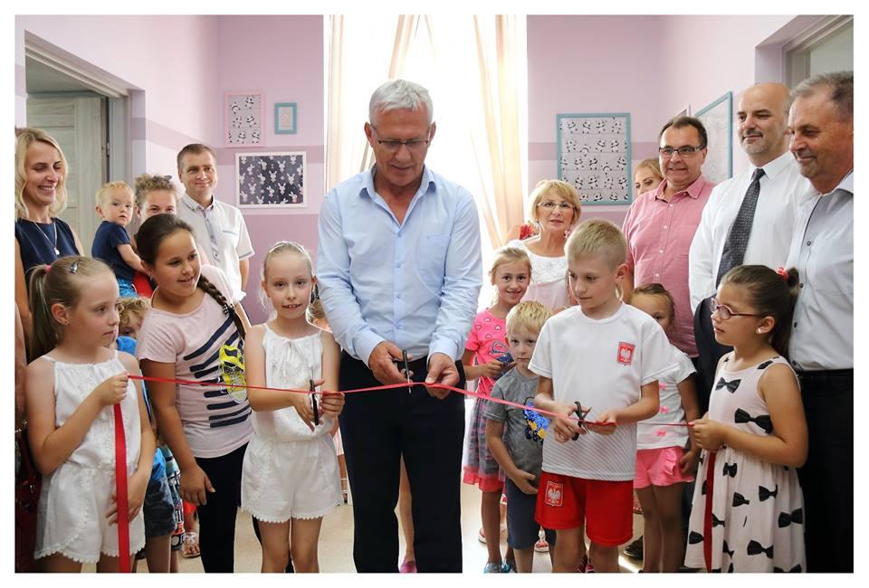 Obraz przedstawia uroczyste przecięcie czerwonej wstęgi przez burmistrza gminy Radłów oraz wychowanków SPWD.