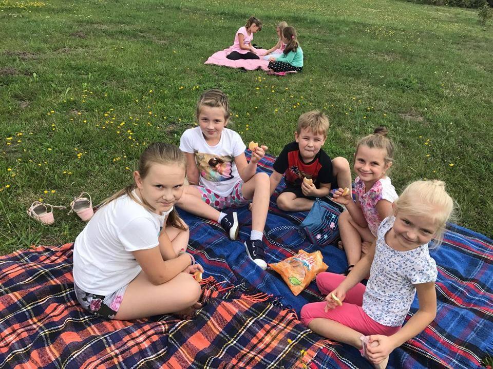 Zdjęcie przedstawia dzieci siedzące na kocach położonych na trawie podczas pikniku.