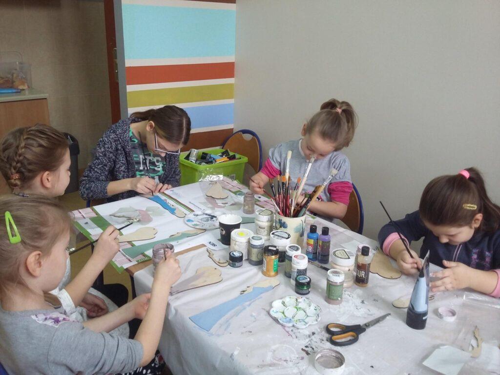 Zdjęcie przedstawia dzieci z placówki przy stole z białym nakryciem tworzących kolejne rękodzieła.