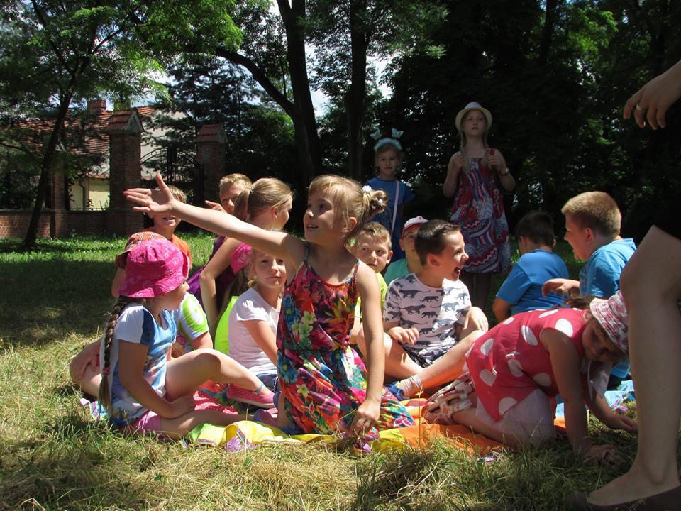 Zdjęcie przedstawia dzieci z placówki na zewnątrz w otoczeniu drzew podczas warsztatów z komunikacji