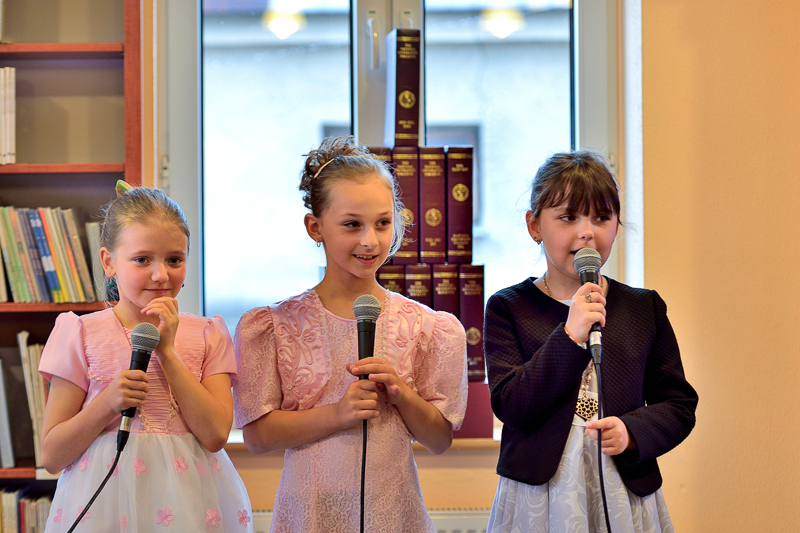 Zdjęcie przedstawia trzy dziewczynki śpiewające piosenkę na dzień Matki