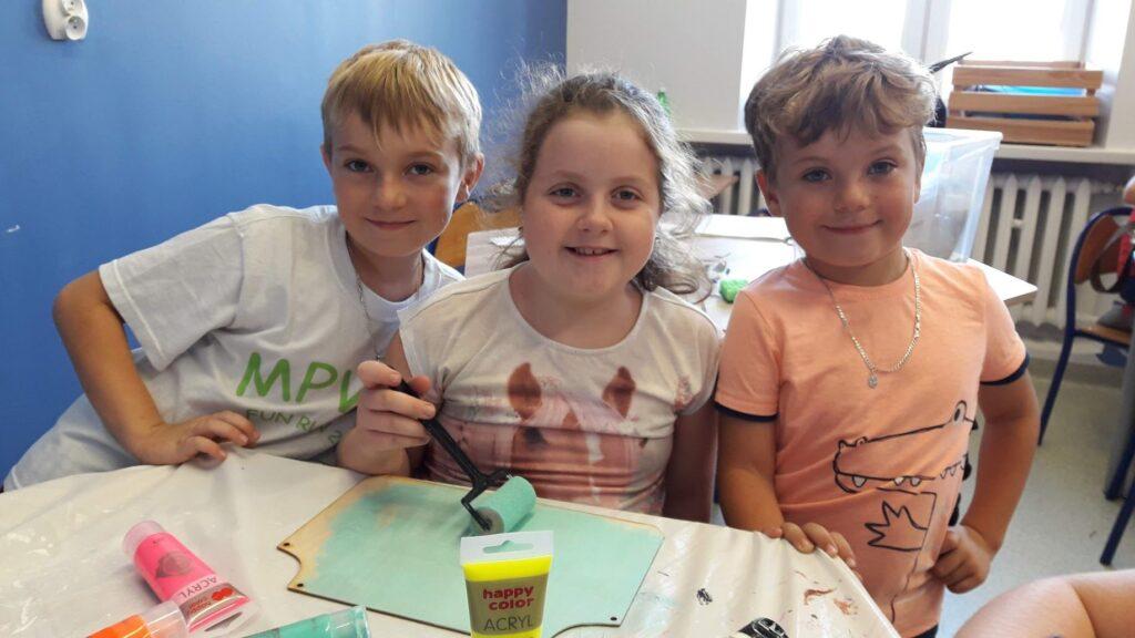 Obraz przedstawia wychowanków SPWD podczas zajęć artystycznego rękodzieła.