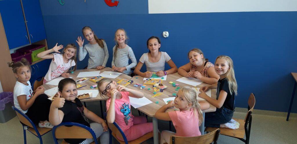 Obraz przedstawia wychowanków SPWD podczas zajęć artystycznych, na których malują, rzeźbią, czy projektują modelinowe breloczki.