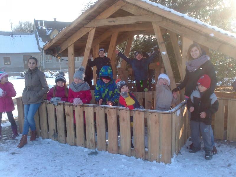 Obraz przedstawia dzieci z placówki cieszące się śniegiem. Pozują do zdjęcia w niewielkim drewnianym budynku.