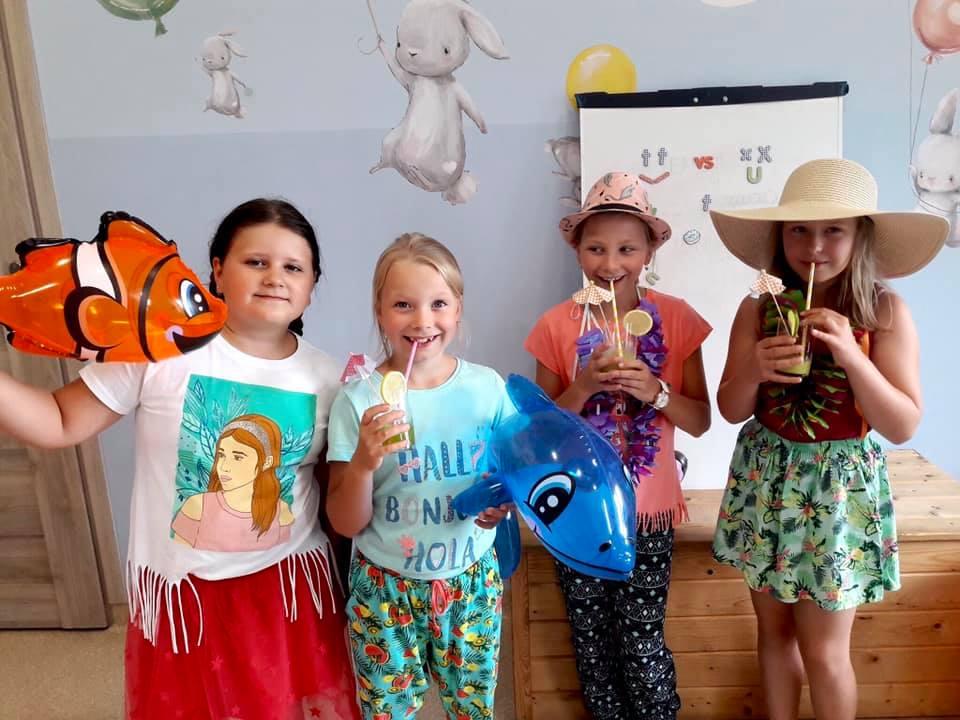 Obraz przedstawia dzieci przebrane w ubrania nawiązujące do Hawajów. Na obrazie można również zobaczyć różnego rodzaju akcesoria związane z Hawajami.