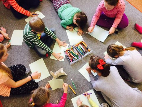 Zdjęcie przedstawia dzieci malujące na kartkach siedząc na dywanie. Zdjęcie jest zrobione z góry.