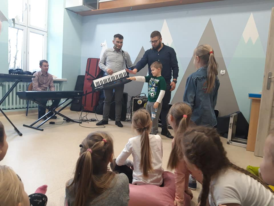 Obraz przedstawia naszych wychowanków podczas audycji muzycznej. Na zdjęciu możemy ujrzeć różnego rodzaju instrumenty muzyczne.