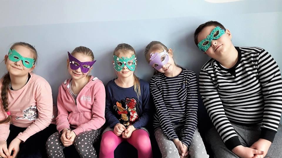 Obraz przedstawia wychowanków w maskach karnawałowych.